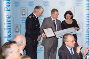 Neal Ingram (centre) receives the team award from the Chief Constable and cheque from the Police and Crime Commissioner